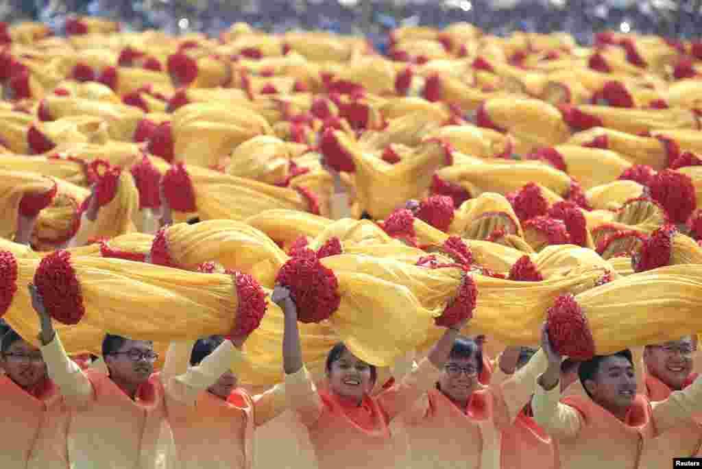 پریڈ کے شرکأ پیلے اور سرخ رنگ کے کپڑے سے بنے پھولوں کو ہوا میں لہراتے ہوئے آگے بڑھ رہے ہیں۔