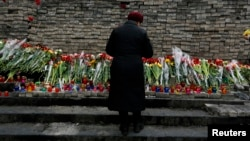 "FILE - A woman mourns before a memorial to those killed in violence in Kyiv, Feb. 25, 2014 — the day that parliament voted to send fugitive President Viktor Yanukovich to be tried by the International Criminal Court for ""serious crimes."""