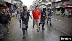 Nepalese police personnel detain a protester (C) during a general strike organized by the Nepal Federation of Indigenous Nationalities (NEFIN) demanding autonomous regions based on ethnicity to be drafted into the new constitution in Kathmandu, Nepal, Aug. 24, 2015.