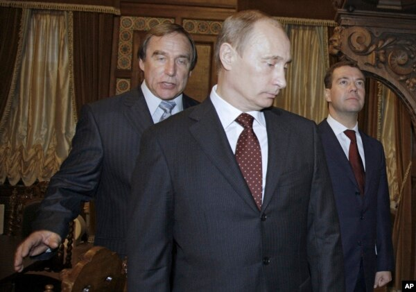 FILE - Russian cellist and House of Music Director Sergei Roldugin, left, escorts then Russian Prime Minister Vladimir Putin, center, and President Dmitry Medvedev as they tour a restored House of Music, a former palace of Great Prince Alexei Alexandrovich Pomanov, in St. Petersburg, Nov. 21, 2009.