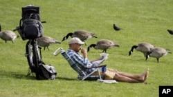 미국 오리건주 포틀랜드 윌래메트 강변에 위치한 톰맥콜 수변공원에서 한 남성이 자전거를 세워둔 채 신문을 읽고 있다.