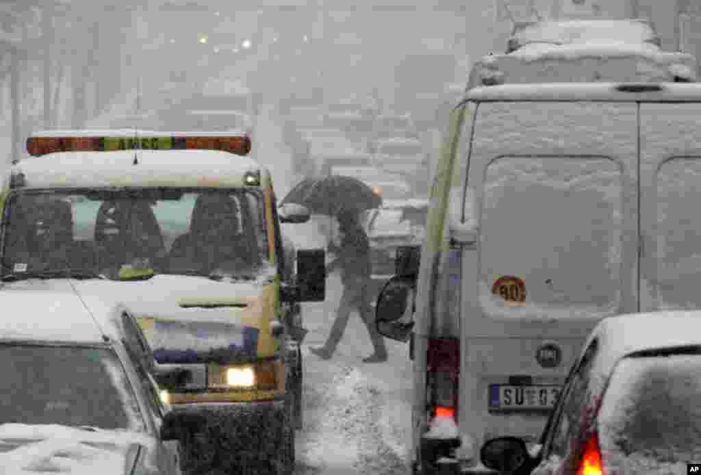 A man walks through snow-covered traffic on a street in Belgrade, Serbia, February 3, 2012. (AP)