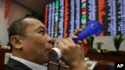 Pialang saham Filipino meniup terompet di Bursa Saham Makati, Manila, menjelang akhir tahun 2013. (Foto: Dok)