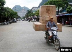 FILE - A man transports boxes of Chinese goods at Tan Thanh market, on the border with China, in Vietnam's northern Lang Son province, July 30, 2014.