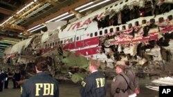 Agen-agen FBI dan polisi New York menjaga rekonstruksi kecelakaan pesawat TWA penerbangan 800 di Calverton, New York, setahun setelah pesawat itu meledak pada 1996. (Foto: Dok)