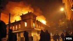 Para demonstran yang marah atas langkah-langkah penghematan membakar sebuah gedung bioskop di Athena (12/2).