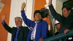 Presiden Bolivia Evo Morales (tengah) menyapa pendukungnya dari balkon istana presiden di La Paz, Bolivia, Minggu (12/10). (AP/Enric Marti)
