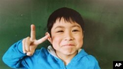 In this undated photo released Friday, 7-year-old Yamato Tanooka was shown at his elementary school. He was found safe Friday nearly a week after he was abandoned in the forest by his parents in northern Japan. (Hamawake Elementary School/Kyodo News via AP)
