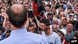 Kosovo's Albanians protest outside the parliament building in Pristina, Sept. 1, 2016. The protesters cheered as as the government withdrew a controversial draft law on a border demarcation agreement with Montenegro.