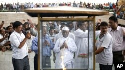 Veteran Indian social activist Anna Hazare (C) prays at the Mahatma Gandhi memorial at Rajghat in New Delhi August 19, 2011.