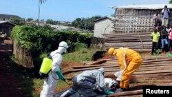 在利比里亚弗里敦,卫生工作者把一名死于埃博拉的妇女的遗体移走。(2014年10月14日)