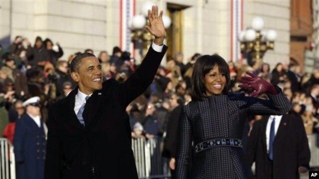 21일 미국 워싱턴에서 바락 오바마 대통령 2기 취임식이 열린 가운데, 취임 기념 행진 중 차량에서 내려 거리에 나온 시민들에게 손을 흔드는 오바마 대통령(왼쪽)과 부인 미셸 오바마 여사.