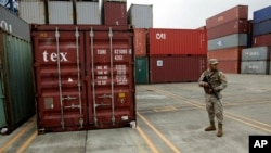 FILE - A police officer stands guard aboard the North Korean-flagged freighter Chong Chon Gang, at the Manzanillo International container terminal on the coast of Colon City, Panama, Wednesday, July 17, 2013. North Korea on Wednesday repeated Cuba's assertion th