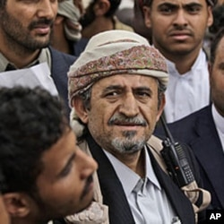 The head of the powerful Hashid tribe, Sheikh Sadique al-Ahmar, center, surrounded by guards, attends the funerals of tribesmen, who were killed in clashes with Yemeni security forces, in Sana'a, May 27, 2011.
