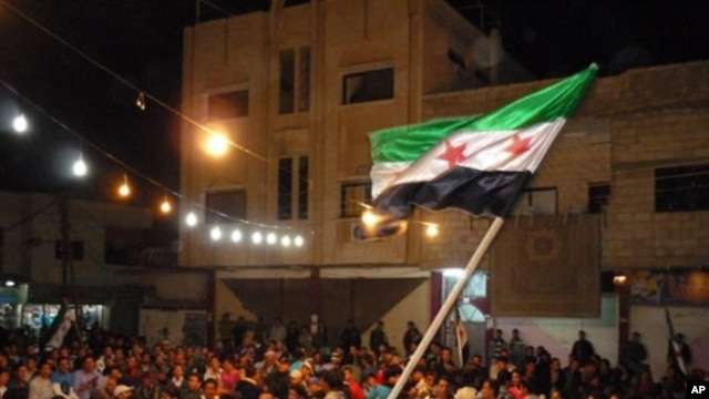 A handout picture released by the Syrian opposition's Shaam News Network shows a Syrian protester waving a pre-Baath Syrian flag during an anti-regime demonstration in Dael in the southern Daraa province late on April 12, 2012.