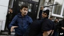 Seorang warga sipil, kiri, dan seorang petugas keamanan memukul seorang pengunjuk rasa saat polisi anti huru-hara menggunakan meriam air untuk membubarkan orang-orang yang berunjuk rasa terhadap penahanan 12 anggota parlemen dari partai pro-Kurdi, HDP (5/11). Istanbul, Turki. (foto: AP Photo/Cagdas Erdogan)
