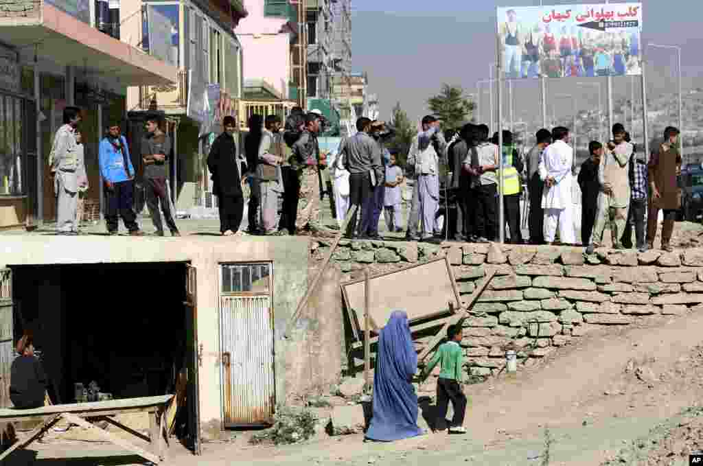 People observe the site of a suicide attack in the deputy counter-narcotic compound in Kabul, Afghanistan, Tuesday, July 22, 2014.