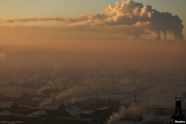 FILE - Power plant chimneys stand behind a coal-burning neighborhood covered in a thick haze on the outskirts of Ulaanbaatar, Mongolia, Jan. 19, 2017.