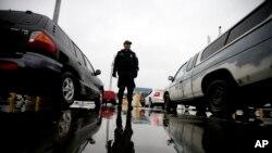 Agen penegakan hukum imigrasi dan bea cukai mengawasi mobil-mobil yang akan memasuki AS dari Tijuana, Meksiko, di San Diego.