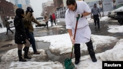 A man shovels snow in the Williamsburg neighborhood in the Brooklyn borough of New York, Feb. 15, 2014.
