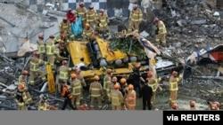 Petugas penyelamat Korea Selatan mencari para penumpang bus yang tertimpa reruntuhan gedung di Gwangju, Kamis (9/6).