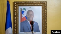 FILE - A picture of the late Haitian President Jovenel Moise hangs on a wall before a news conference by interim Prime Minister Claude Joseph, in Port-au-Prince, Haiti, July 13, 2021.