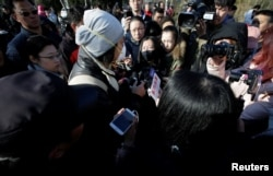 A parent is surrounded by members of the media outside the kindergarten run by preschool operator RYB Education Inc being investigated by police, in Beijing, China, Nov. 24, 2017.