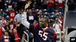 Ancien centre NBA Dikembe Mutombo conduit les Texans de Houston sur le terrain avant un match de football de la NFL contre les Ravens de Baltimore dimanche, 21 décembre 2014, à Houston.