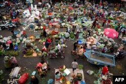A crowd of people and vendors are seen at a market in Phnom Penh on February 1, 2021. (Photo by TANG CHHIN Sothy/AFP)