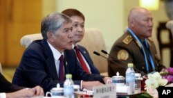 FILE - Kyrgyz President Almazbek Atambayev, left, talks with Chinese President Xi Jinping during a meeting at Diaoyutai State Guesthouse in Beijing, China, Sept. 2, 2015.