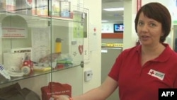 Працівниця Червоного Хреста демонструє набір речей першої необхідності при землетрусі