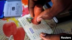 Un agent électoral appose le sceau sur le bulletin d'un électeur qui vient de voter lors des législatives à Abidjan, Côte d'Ivoire, 18 décembre 2016.