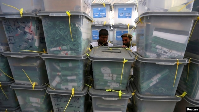 FILE - Afghan electoral workers sort ballot boxes at a counting center in Kabul.