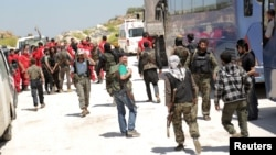 "Fighters from a coalition of rebel groups called ""Army of Fatah"" and members of the Syrian Arab Red Crescent stand near buses and ambulances on the outskirts of Idlib city, preparing to enter the two besieged Shi'ite towns of al-Foua and Kefraya to evacu"