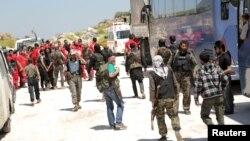 ادلب کے باہر شامی عرب ریڈ کریسنٹ کے اہلکار اور باغی جنجگو الفوعا اور کیفریا سے لوگوں کو لانے والی ایک بس کے قریب کھڑے۔