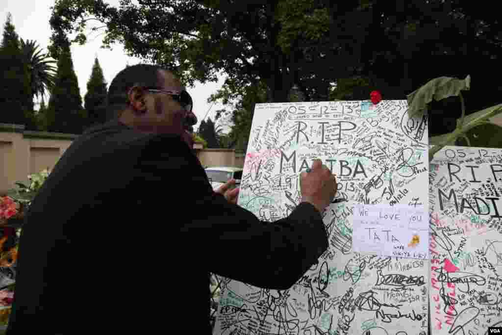 Fãs de Mandela deixam tributo à porta da sua antiga casa em Houghton, África do Sul. (Hannah McNeish para VOA)