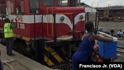 Uma mulher coloca uma mala na cabeça de outra na estação de Caminhos de Ferro de Moçambique, em Moatize