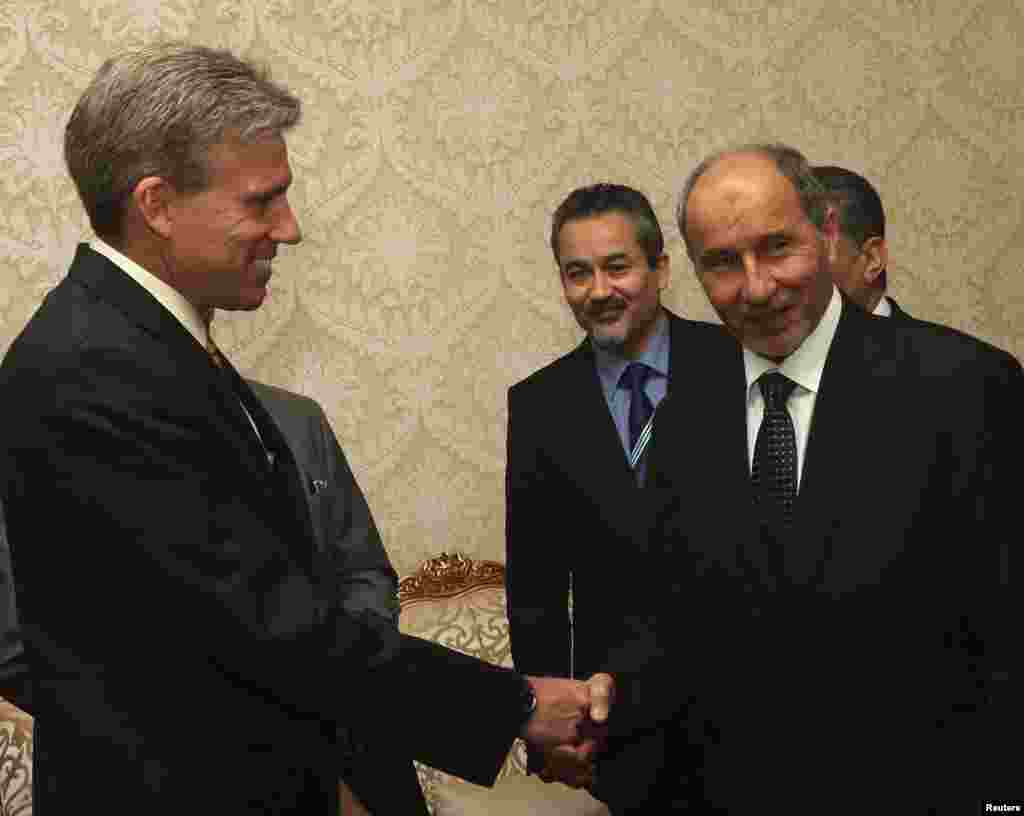John Christopher Stevens, newly appointed U.S. ambassador to Libya, shakes hands with Libyan National Transitional Council (NTC) chairman Mustafa Abdel Jalil (R) after presenting his credentials during a meeting in Tripoli, June 7, 2012.