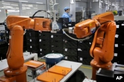 FILE - A Chinese worker is seen behind orange robot arms at Rapoo Technology factory in the southern Chinese industrial boomtown of Shenzhen, Aug. 21, 2015. Automation could wipe out two thirds of jobs in some countries, the World Bank warns.
