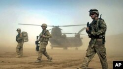 U.S. soldiers participating in the NATO- led International Security Assistance Force (ISAF) walk ahead of a Chinook helicopter near the place where the foundation of a hospital was laid in Shindand, Herat, west of Kabul, Afghanistan, January 28, 2012