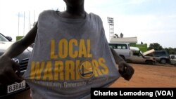 A fan shows off his T-shirt, donated by NBA champs the Golden State Warriors, at the inaugural Manute Bol basketball tournament in Juba, South Sudan.