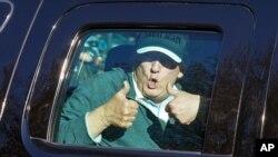 El presidente Donald Trump saluda a sus partidarios al salir de su club privado de golf en Sterling, Virginia, el domingo, 8 de noviembre de 2020.