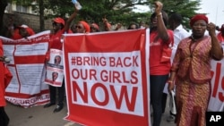 People attend a demonstration calling on the government to rescue the kidnapped girls of the government secondary school in Chibok, in Abuja, Nigeria, Oct. 14, 2014.