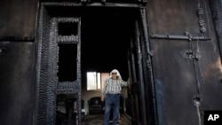 Dalam sebuah foto yang diambil tanggal 31 Juli 2015 ini, seorang warga Palestina memeriksa rumahnya yang dicurigai dibakar oleh para pemukim Yahudi, menewaskan bayi Palestina berusia 18 bulan dan kedua orang tuanya di desa Duma dekat Tepi Barat kota Nablus. Israel pada hari Minggu (3/1) mendakwa dua ekstrimis Yahudi yang dicurigai melakukan serangan tersebut.