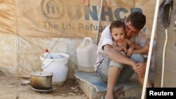 Hai cha con người Syria tại trại tị nạn Al Zaatri ở thành phố Mafraq của Jordan gần biên giới Syria