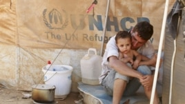 A Syrian refugee holds his child as he sits by his tent at Al Zaatri refugee camp in the Jordanian city of Mafraq, near the border with Syria, Sept. 9, 2012.