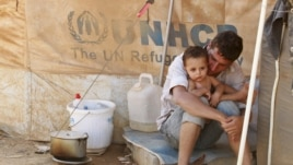 A Syrian refugee holds his child as he sits by his tent at Al Zaatri refugee camp in the Jordanian city of Mafraq, near the border with Syria, September 9, 2012.