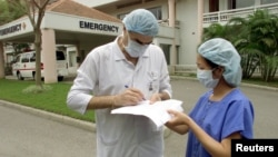 Lucien Blanchard, general manager of the Vietnam-France Hospital, signs a form for a nurse outside the facility in capital city Hanoi, March 2003.