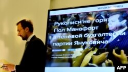 FILE - Member of Ukraine's parliament and former journalist Serhiy Leshchenko holds papers in front of a screen displaying a picture of Donald Trump's former presidential campaign chairman Paul Manafort during a press conference in Kyiv, Ukraine, Aug. 19, 2016.