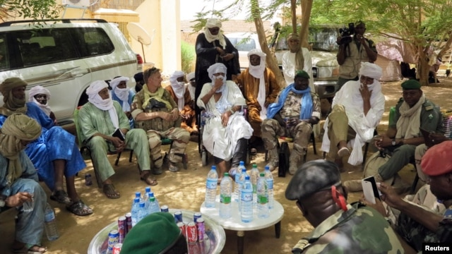 FILE - A delegation of Malian, French and UN army officers greet separatist rebel patriarch Intallah Ag Attaher (C, in white) in Kidal, June 23, 2013.